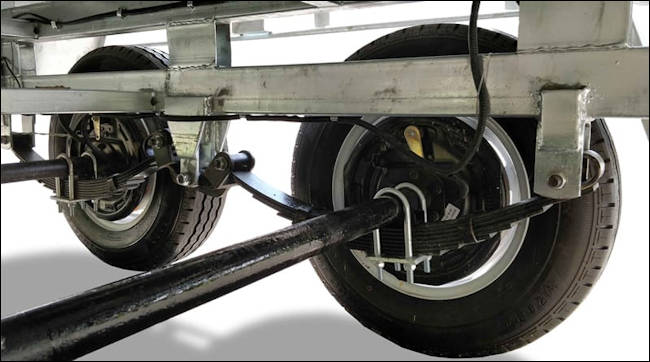 Flat top trailer under carriage showing axle, wheels, springs and brakes - Midway Trailers, Macksville